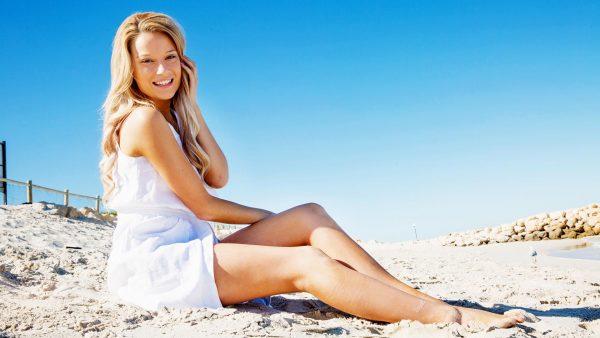 Девушка в белом сарафане сидит на песке