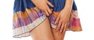 Девушка в синей юбке с оранжевой, фиолетовой и белой полосками чешет лобковую зону