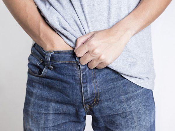 Мужчина в джинсах чешет лобковую зону