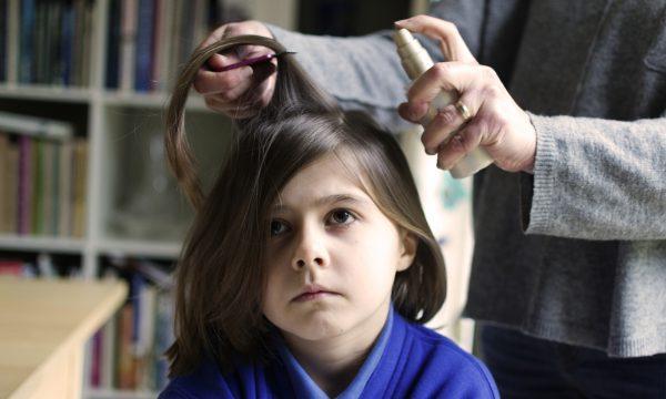 Нанесение спрея на волосы ребёнка