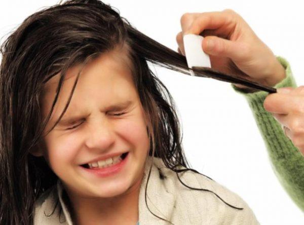 Девочке вычёсывают мокрые волосы