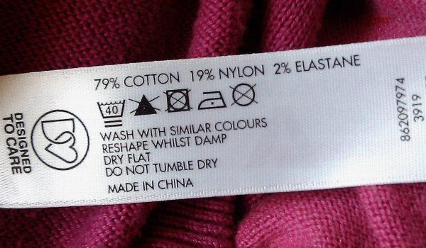 Ярлык на одежде с символами и информацией на английском языке