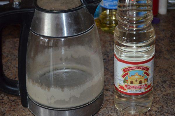 Электрический чайник с накипью и бутылка уксуса