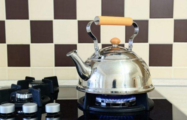 Очищенный чайник из нержавейки стоит на плите