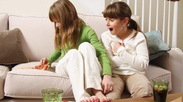 Дети едят пиццу, сидя на диване