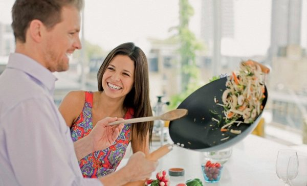 Мужчина готовит в сковороде вок
