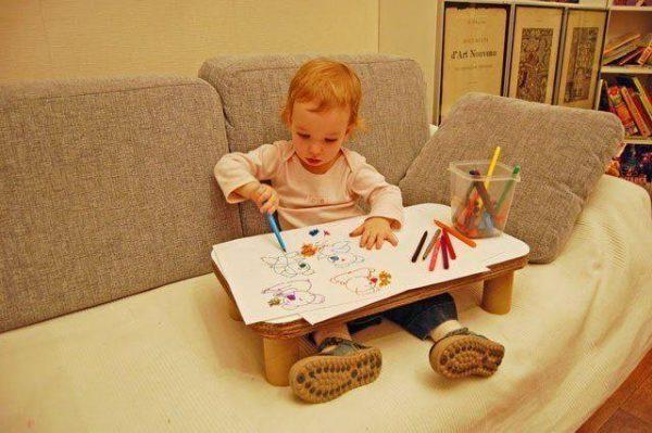 Ребёнок рисует, сидя на диване