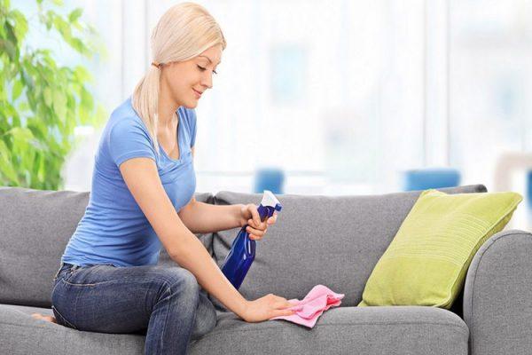Женщина протирает поверхность дивана