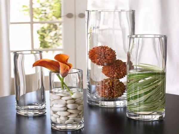 Стеклянные сосуды с водой и декоративными цветами и камнями