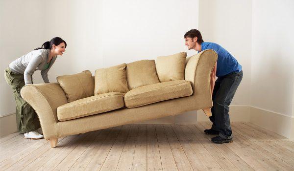 Муж с женой двигают диван