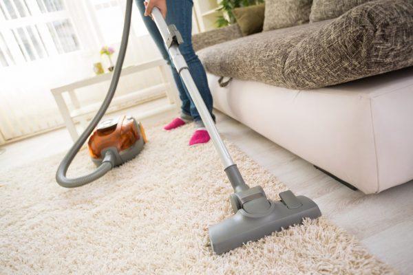 Процесс уборки пылесосом в гостиной