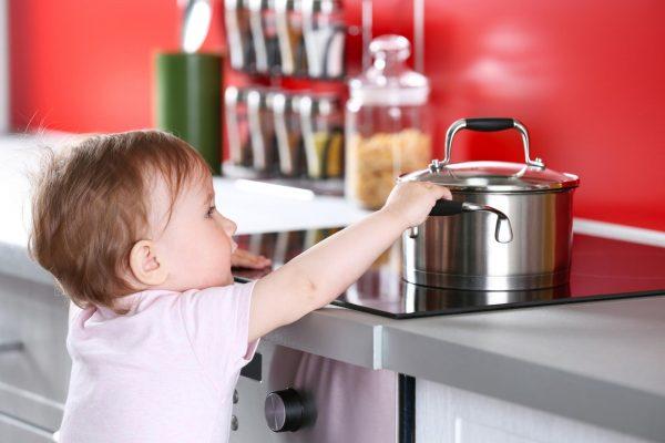 Ребёнок тянется к кастрюле на плите
