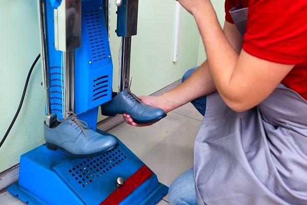 Мастер растягивает обувь