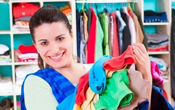 Девушка разбирает шкаф с одеждой