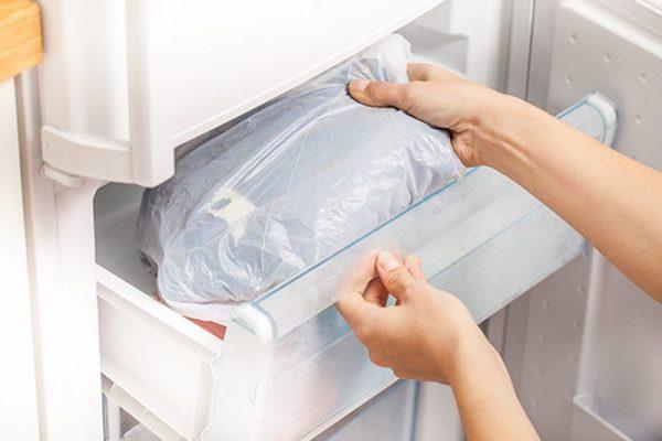 Женщина убирает одежду в морозилку