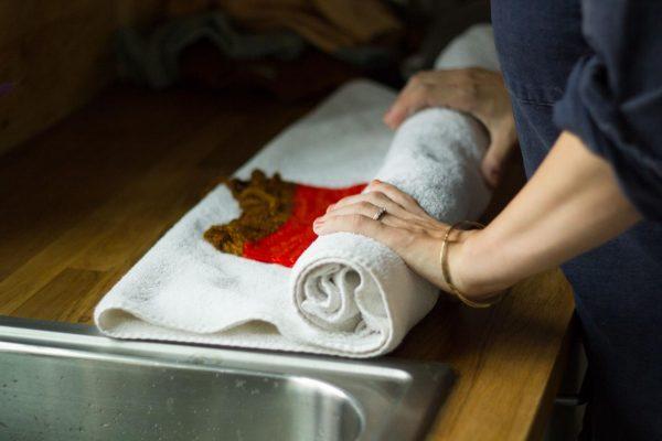 Свитер отжимают через полотенце