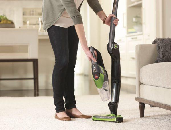 Девушка производит уборку вертикальным моющим пылесосом