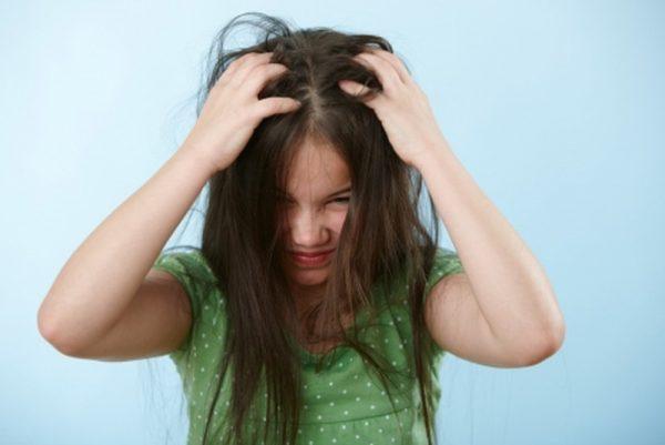 Девочка чешет голову