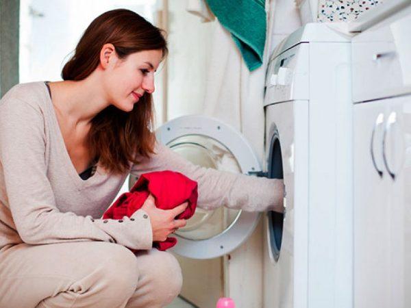 Женщина загружает бельё в машинку
