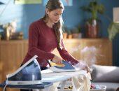 девушка гладит утюгом с парогенератором