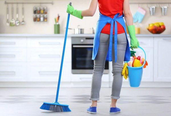 Женщина со щёткой и принадлежностями для уборки в руках