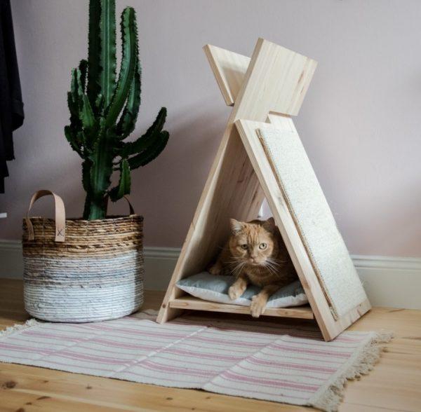 готовый деревянный вигвам с когтеточкой установлен на полу и занят котом