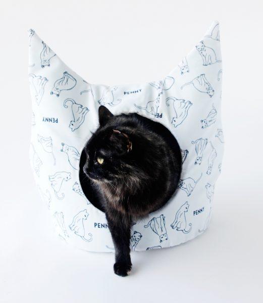 чёрная кошка выходит из домика в форме кошачьей головы, сшитой из белой ткани с рисунком из кошачьих фигур